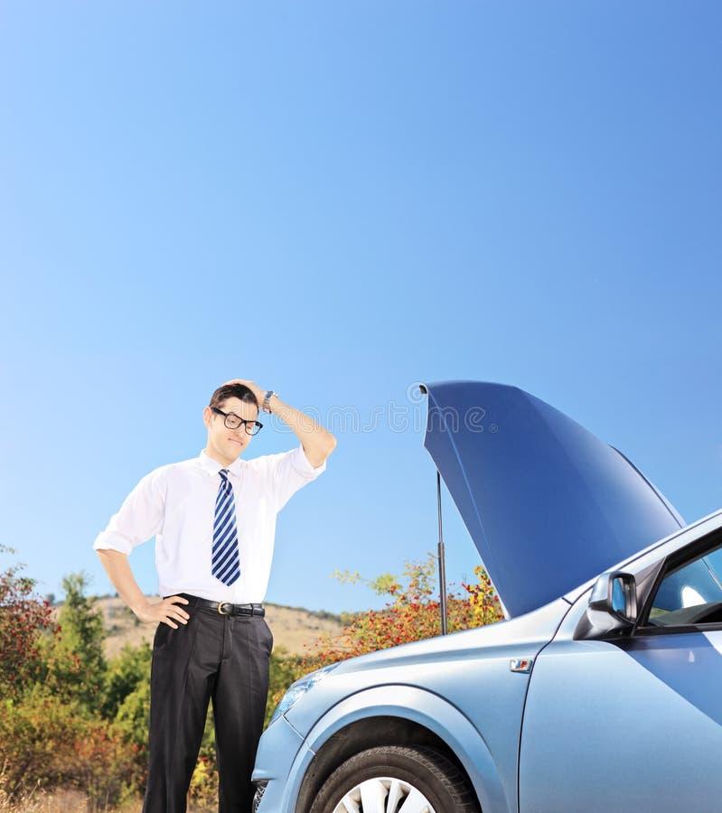 Uomo d'affari che sta vicino alla sua automobile rotta e che pensa che cosa fare fotografia stock libera da diritti