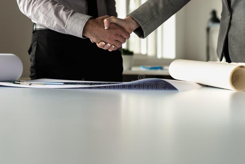 Uomo d'affari che stringe le mani con il suo socio commerciale femminile fotografia stock