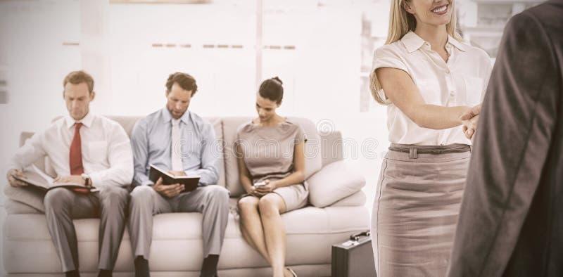 Uomo d'affari che stringe le mani con la donna oltre all'intervista aspettante della gente immagine stock