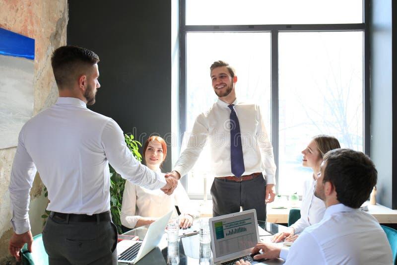 Uomo d'affari che stringe le mani per sigillare un affare con il suoi partner e colleghi in ufficio immagine stock