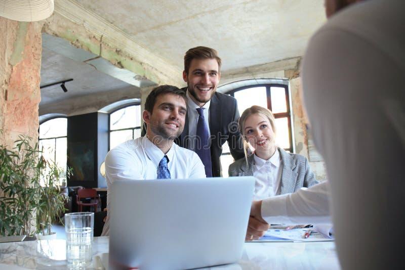 Uomo d'affari che stringe le mani per sigillare un affare con il suoi partner e colleghi in ufficio fotografia stock