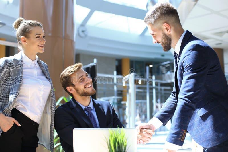 Uomo d'affari che stringe le mani per sigillare un affare con il suoi partner e colleghi in ufficio immagine stock libera da diritti