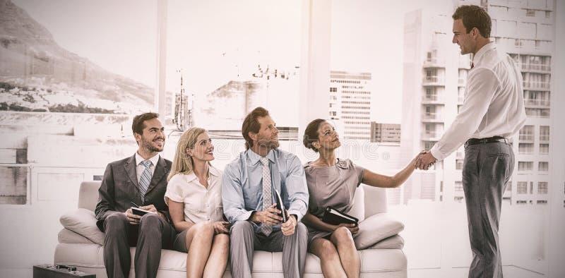 Uomo d'affari che stringe mano con la donna che si siede con l'intervista aspettante della gente fotografia stock