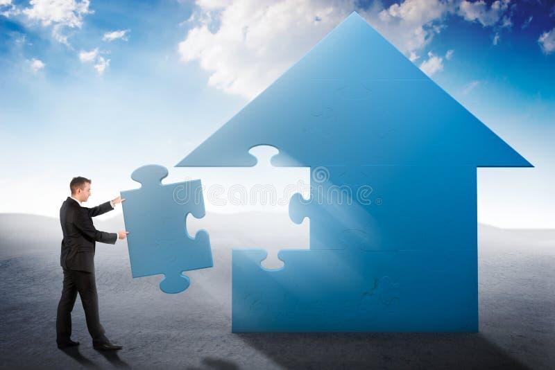 Uomo d'affari che sviluppa un puzzle della casa illustrazione di stock
