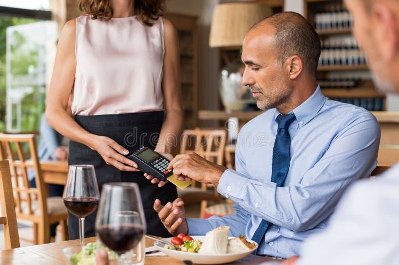 Uomo d'affari che swiping la carta di credito fotografia stock