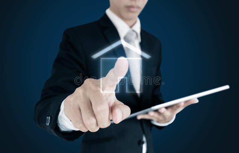 Uomo d'affari che tiene compressa digitale e l'icona commovente della casa sullo schermo, su fondo blu immagine stock