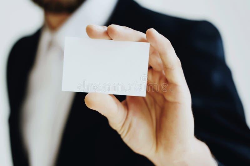 Uomo d'affari che tiene a disposizione biglietto da visita bianco pulito Derisione di orizzontale su, fondo vago fotografia stock