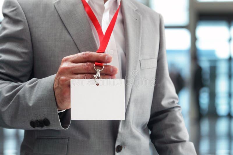 Uomo d'affari che tiene il distintivo in bianco di identificazione fotografie stock