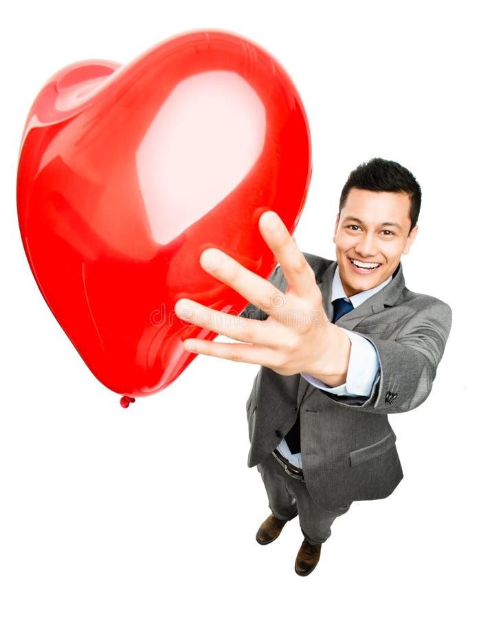 Uomo d'affari che tiene il pallone rosso del cuore fotografia stock