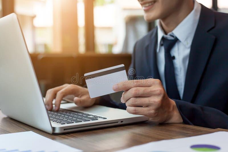 Uomo d'affari che tiene la carta di credito e che per mezzo del computer portatile fotografia stock libera da diritti