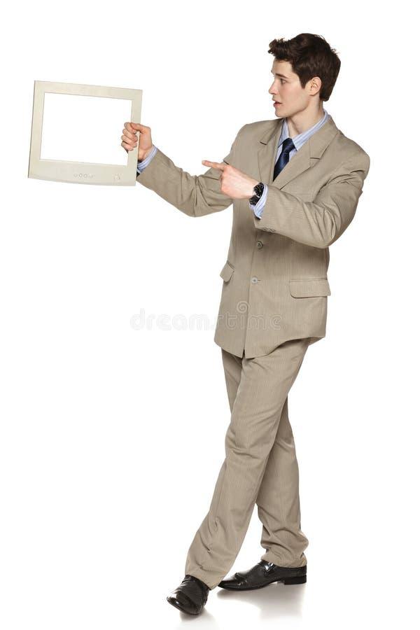 Uomo d'affari che tiene la TV/schermo di computer fotografie stock