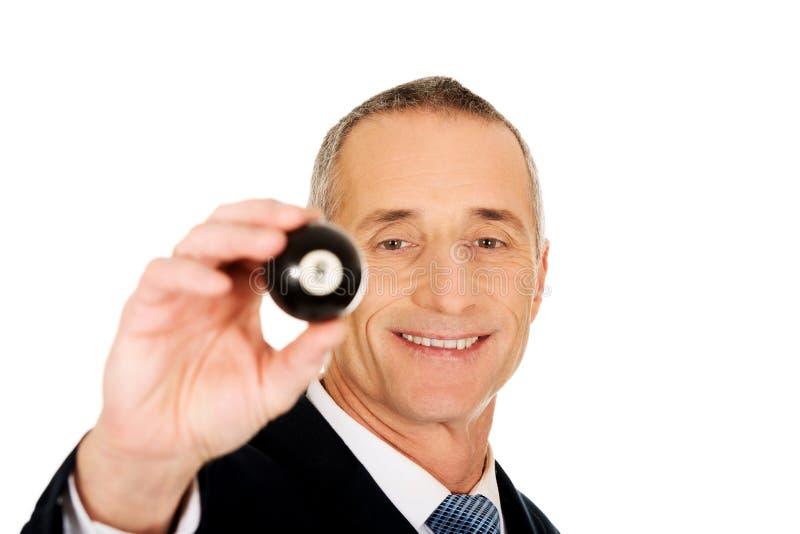 Uomo d'affari che tiene palla da biliardo nera fotografia stock libera da diritti