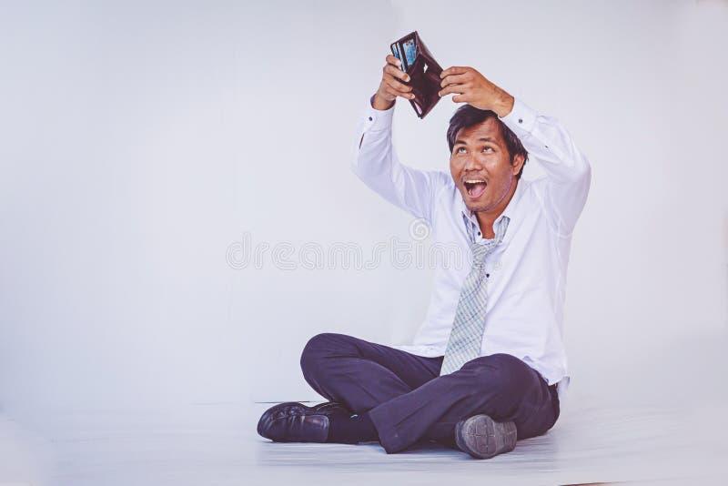 Uomo d'affari che tiene portafoglio vuoto che si siede sul pavimento immagini stock libere da diritti