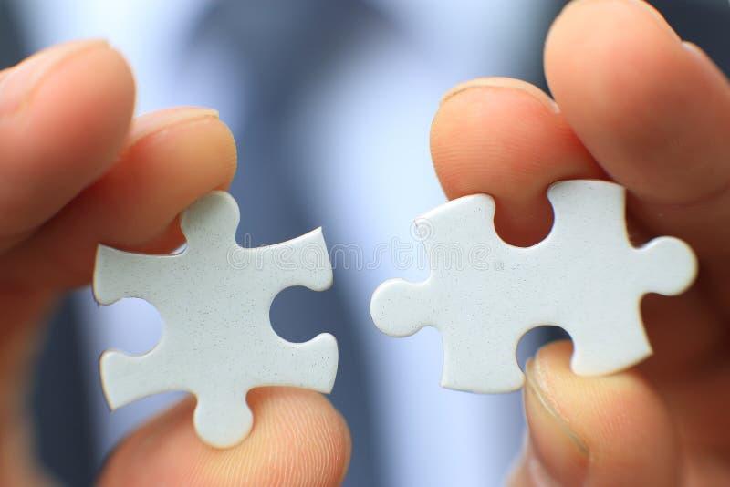 Uomo d'affari che tiene puzzle bianco in bianco due fotografie stock