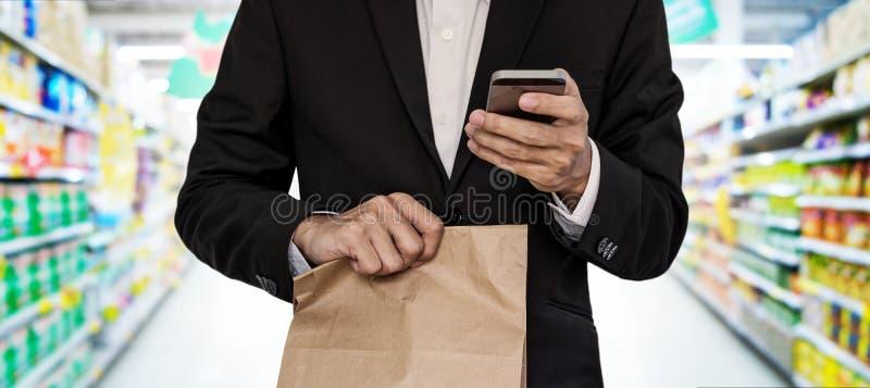 Uomo d'affari che tiene sacco di carta marrone, mentre per mezzo dello Smart Phone al centro commerciale fotografie stock