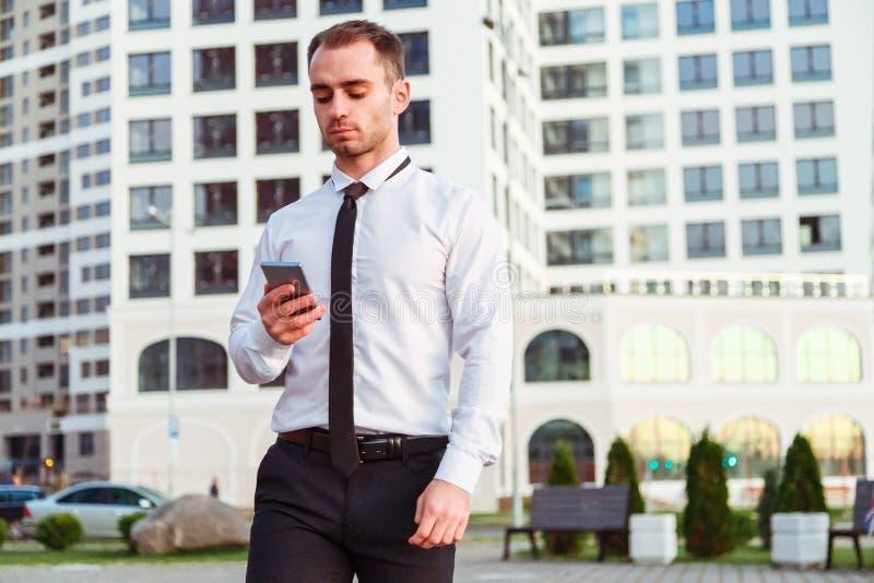 Uomo d'affari che tiene smartphone mobile facendo uso del app fotografie stock