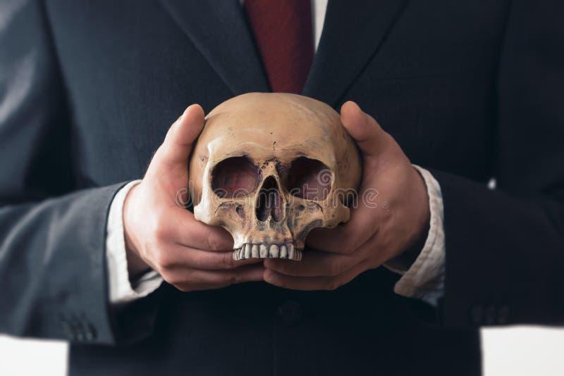 Uomo d'affari che tiene un cranio in sue mani fotografia stock