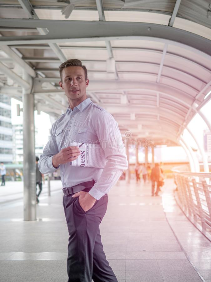 Uomo d'affari che tiene un giornale sul modo lavorare in una mattina contro il contesto di una città moderna fotografie stock libere da diritti