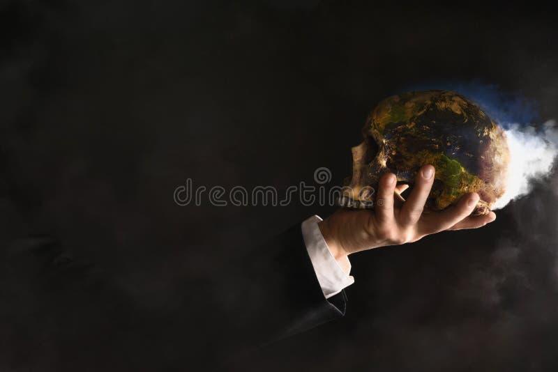 Uomo d'affari che tiene un globo bruciante mentre hanno subito una mutazione in un cranio immagine stock