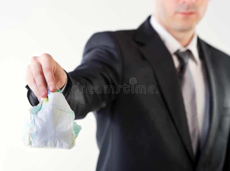 Uomo d'affari che tiene un pannolino sporco fotografia stock libera da diritti