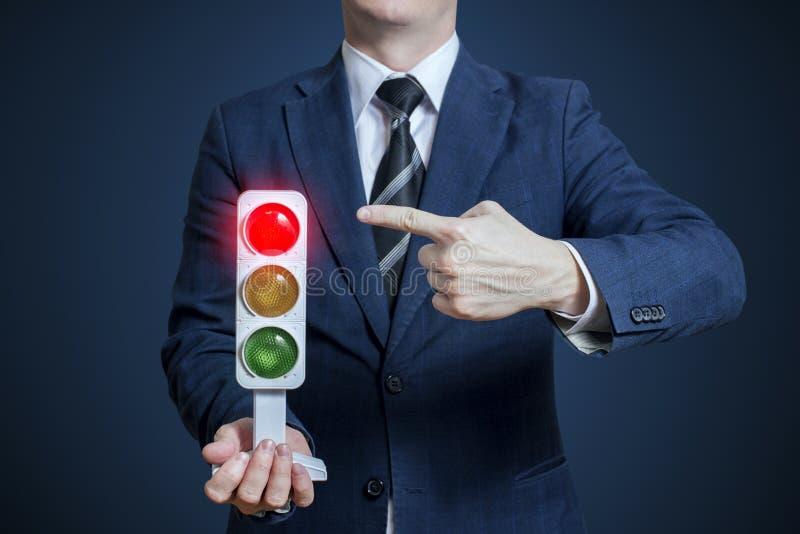 Uomo d'affari che tiene un semaforo con luce rossa sopra immagine stock
