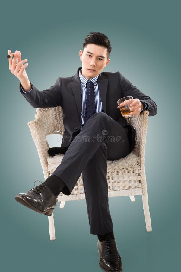 Uomo d'affari che tiene un sigaro immagine stock
