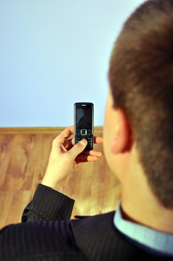 Uomo d'affari che tiene un telefono immagine stock libera da diritti