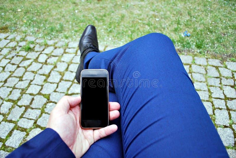 Uomo d'affari che tiene un telefono cellulare e che scrive il messaggio degli sms fotografia stock libera da diritti