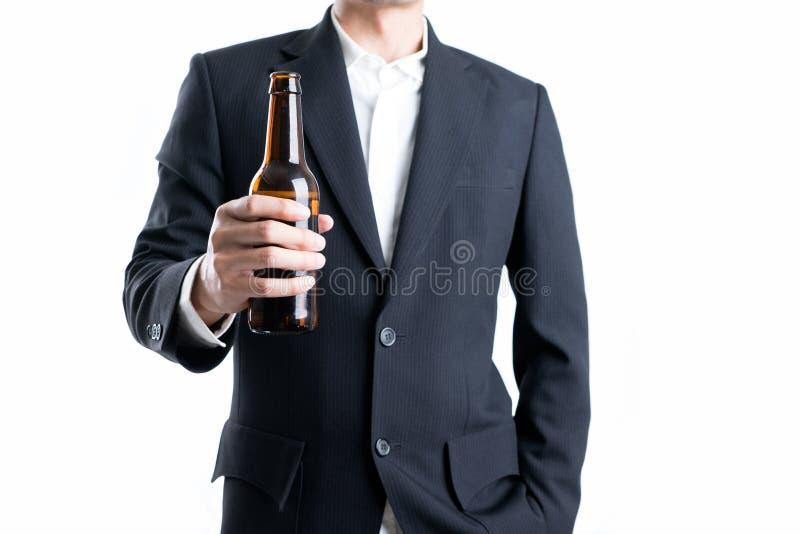 Uomo d'affari che tiene una bottiglia di birra su fondo bianco isolato fotografia stock