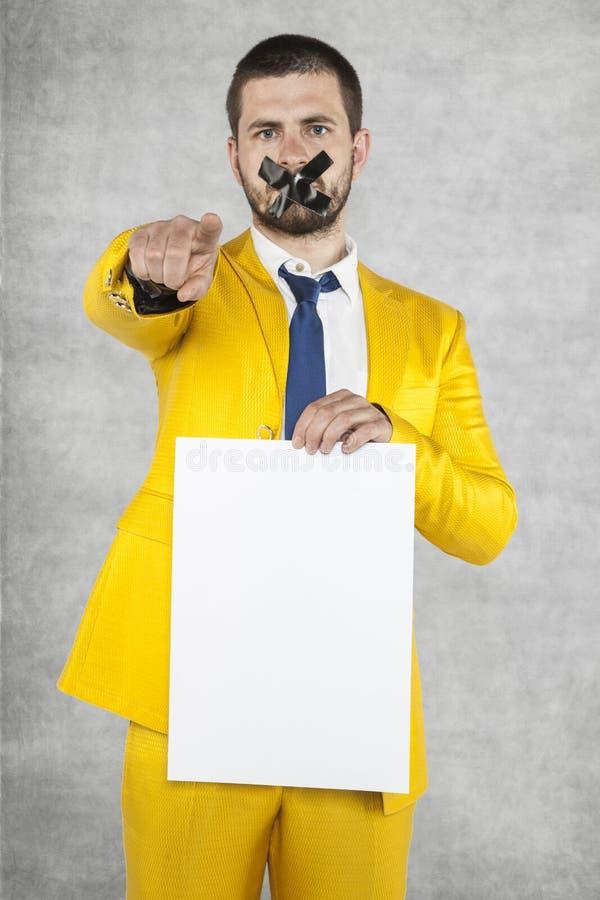 Uomo d'affari che tiene una carta in bianco, punti a voi fotografie stock