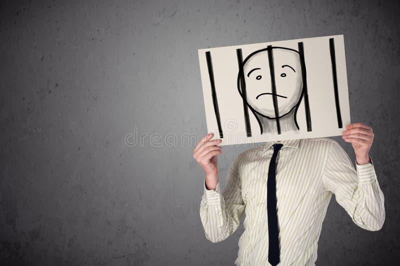 Uomo d'affari che tiene una carta con un prigioniero dietro le barre sopra i immagine stock