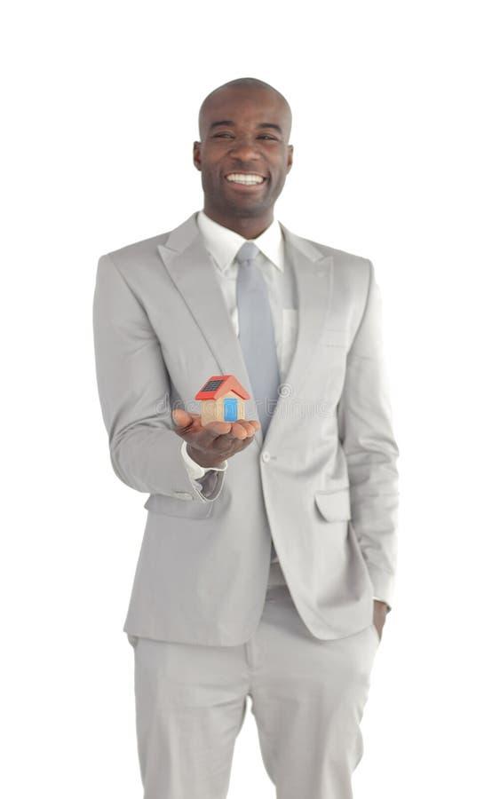 Uomo d'affari che tiene una casa in sue mani immagine stock