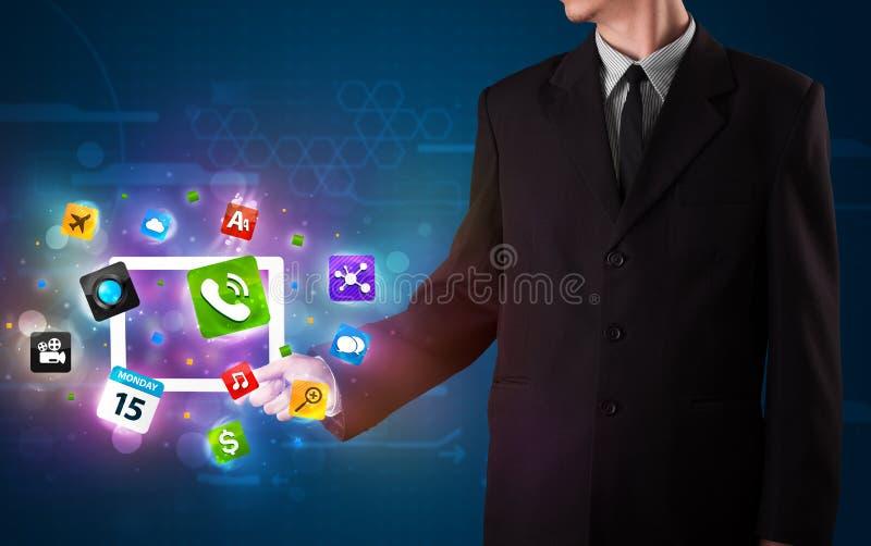 Uomo d'affari che tiene una compressa con i apps e le icone variopinti moderni immagine stock
