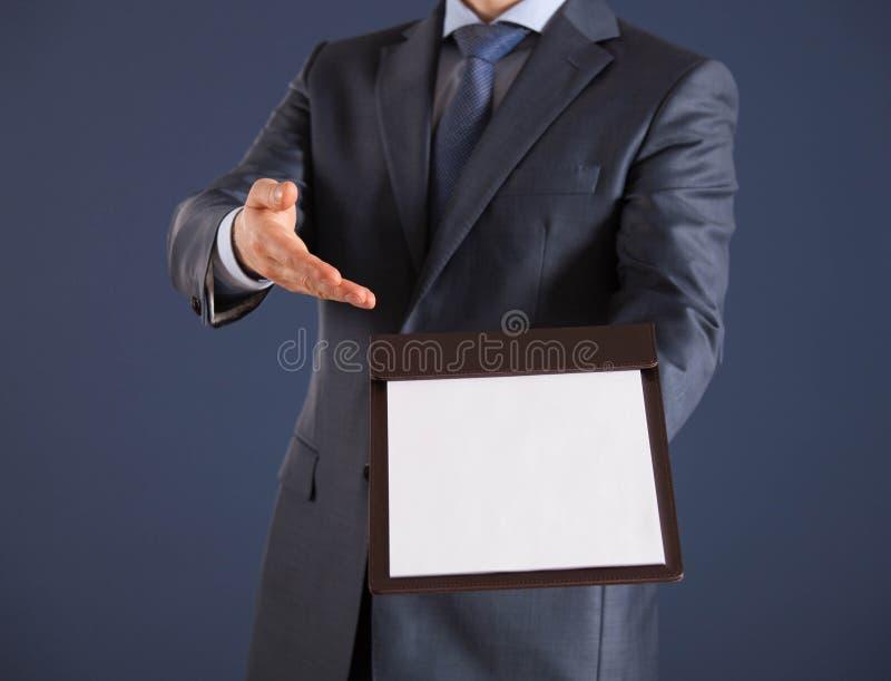 Uomo d'affari che tiene una lavagna per appunti con il foglio di carta vuoto immagini stock
