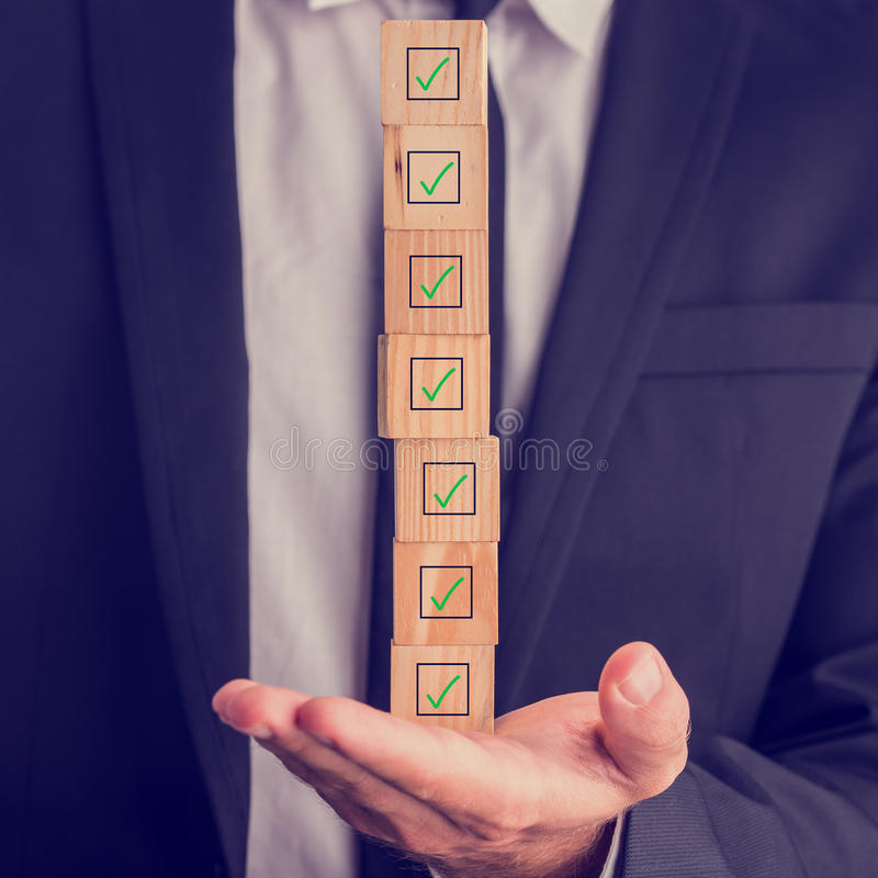 Uomo d'affari che tiene una pila di scatole controllate immagine stock