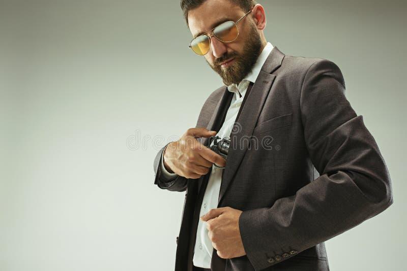 Uomo d'affari che tira la pistola dalla tasca fotografia stock libera da diritti