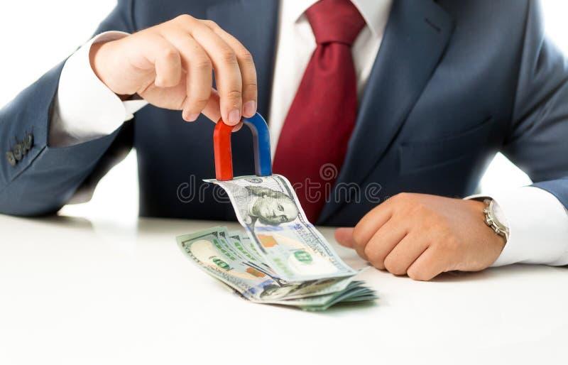 Uomo d'affari che tira soldi dalla pila sulla tavola con il magnete fotografia stock