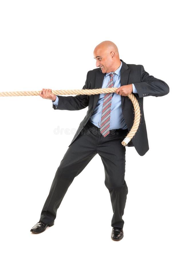 Uomo d'affari che tira una corda fotografia stock libera da diritti