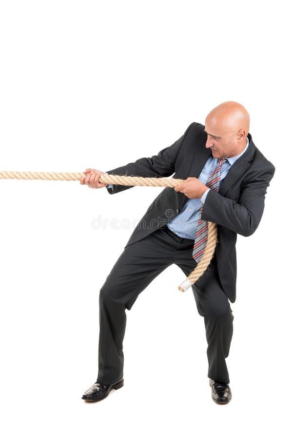 Uomo d'affari che tira una corda immagine stock