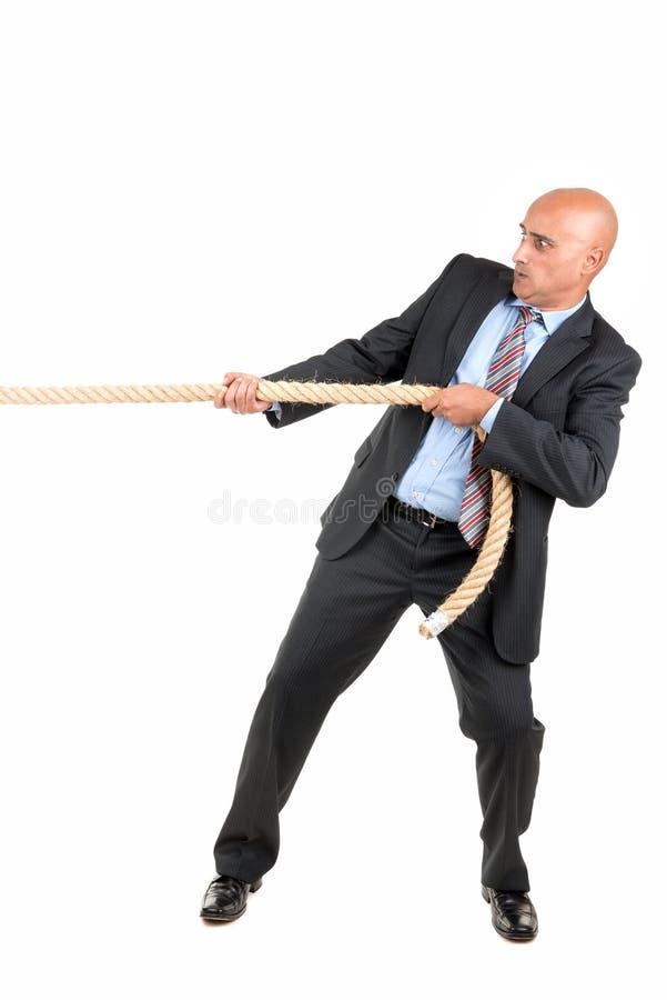 Uomo d'affari che tira una corda fotografia stock