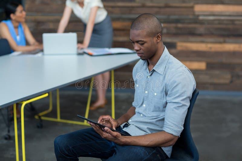 Uomo d'affari che utilizza compressa digitale nell'ufficio immagine stock
