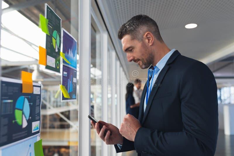 Uomo d'affari che utilizza telefono cellulare vicino alla parete di vetro nell'ufficio immagini stock libere da diritti