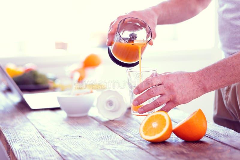 Uomo d'affari che versa arancia sana fresca in vetro prima di andare lavorare fotografia stock