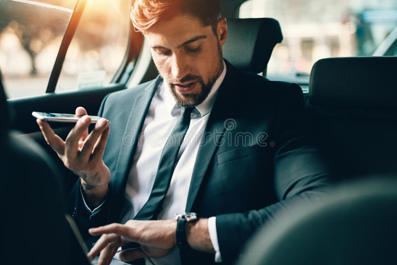 Uomo d'affari che viaggia in macchina facendo uso dello Smart Phone e che controlla Tim immagine stock