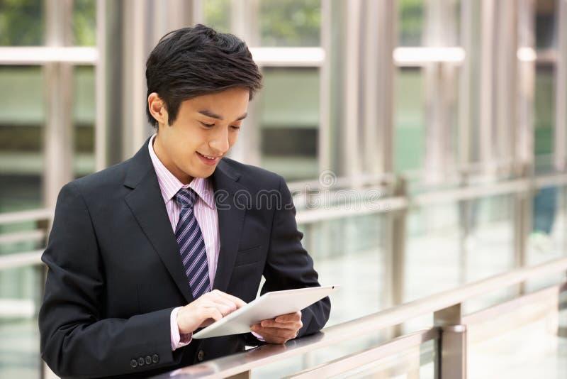 Uomo d'affari cinese che lavora al calcolatore del ridurre in pani fotografia stock