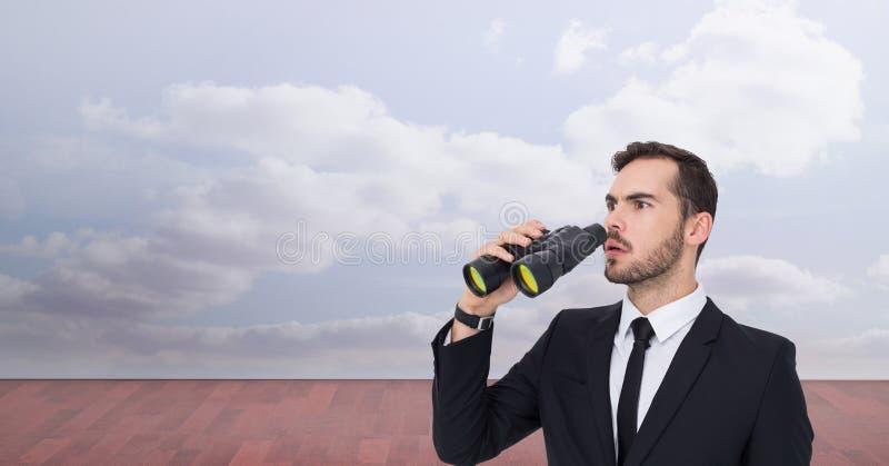 Uomo d'affari colpito che distoglie lo sguardo mentre tenendo il binocolo fotografia stock libera da diritti
