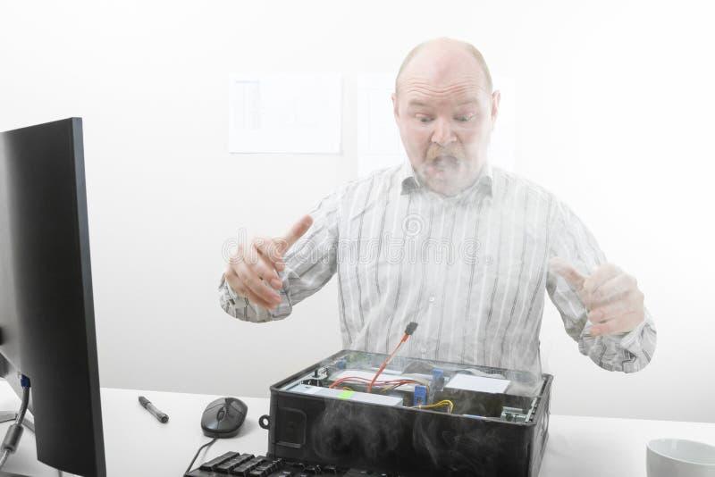 Uomo d'affari colpito Looking At Smoke che proveniente fuori dal computer Ch immagine stock