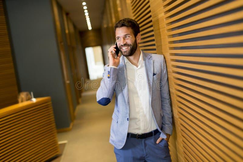 Uomo d'affari in completo che tiene in mano il telefono in ufficio fotografie stock