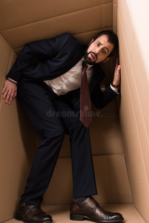 Uomo d'affari con claustrofobia dentro una scatola fotografia stock libera da diritti