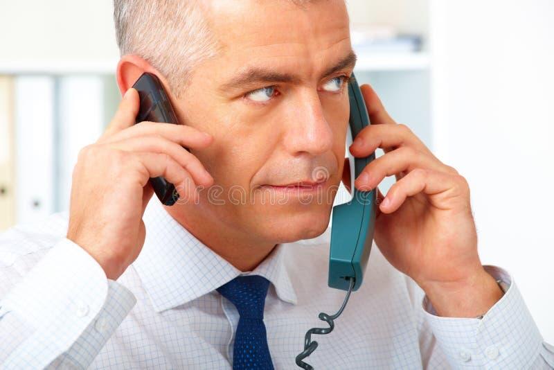 Uomo d'affari con due telefoni fotografie stock